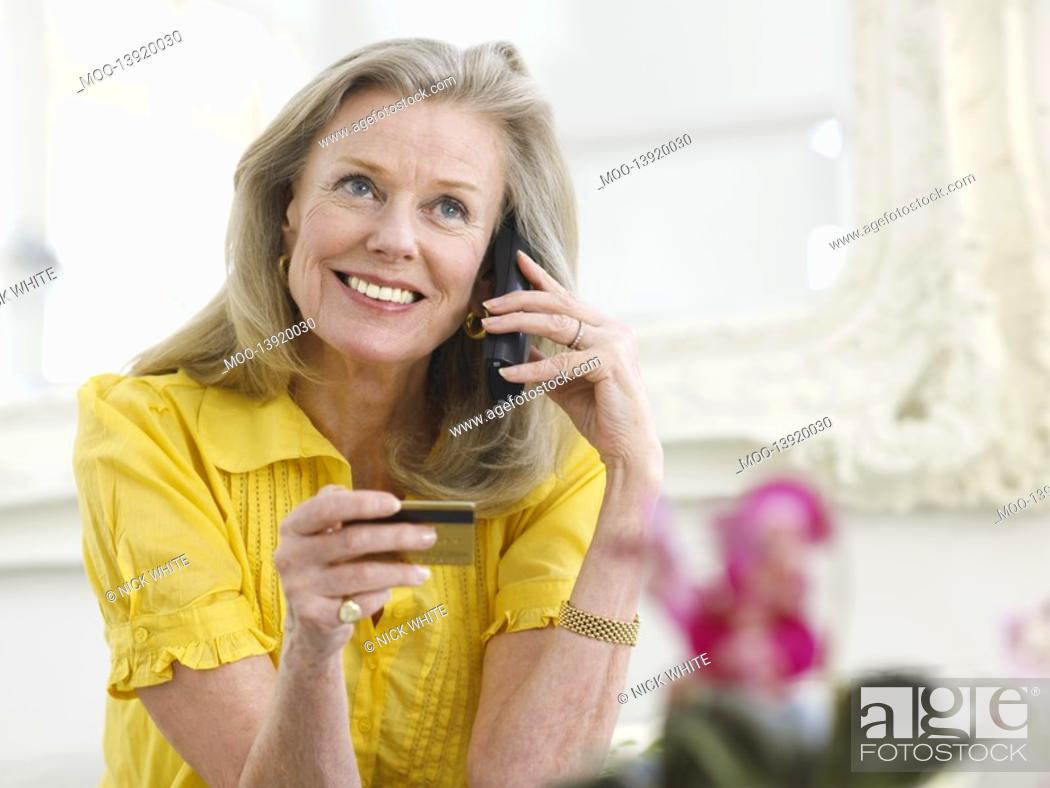 Stock Photo: Woman holding credit card using phone in living room portrait.