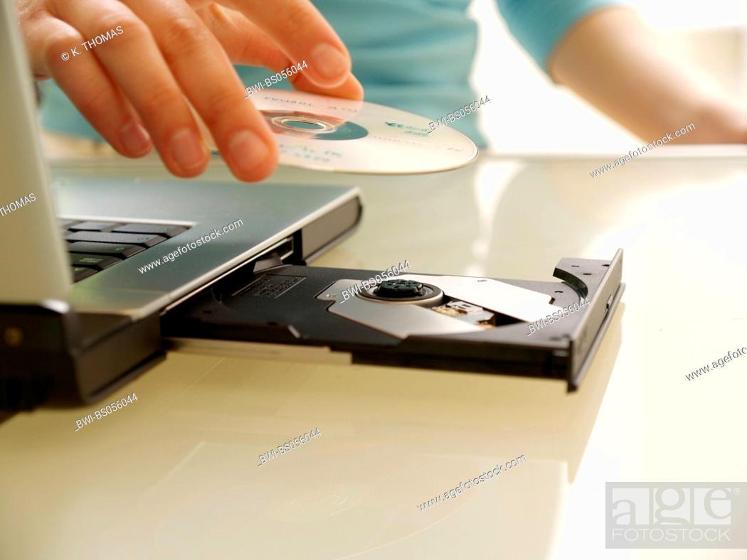 young woman twen hand putting a cd in the cd drive on the laptop