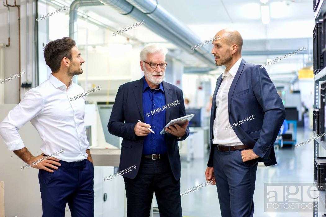 Stock Photo: Senior manager with colleagues discussing over digital tablet while standing at illuminated factory.