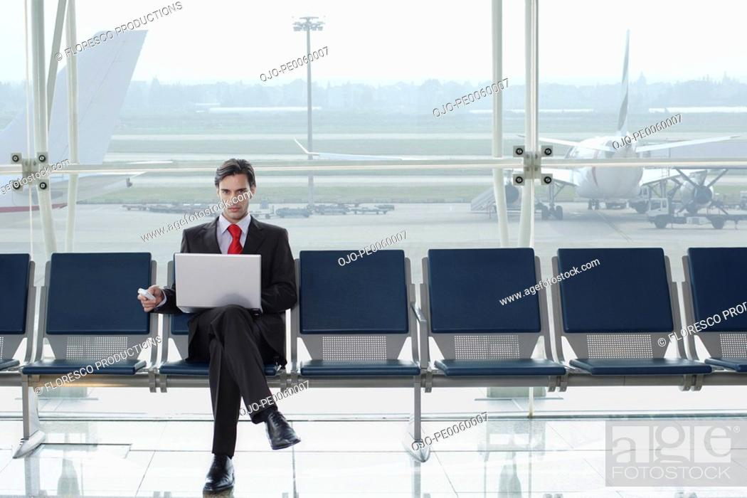 Stock Photo: Businessman in airport with laptop and mobile phone. Barcelona El Prat Airport. Spain.