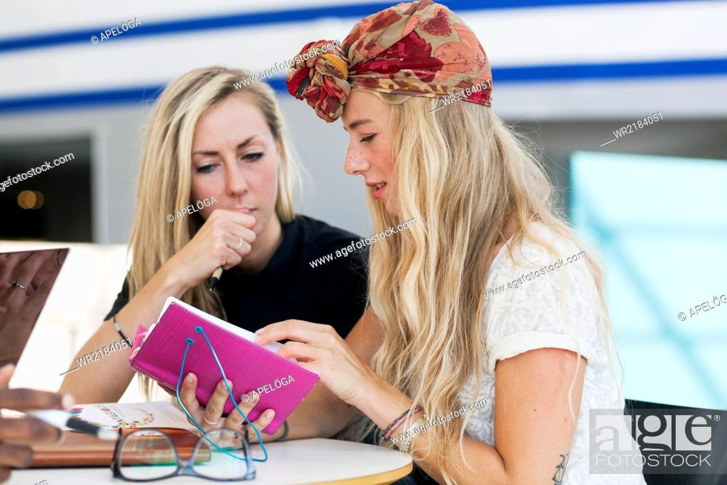 Stock Photo: Female friends reading notes together in college cafe.