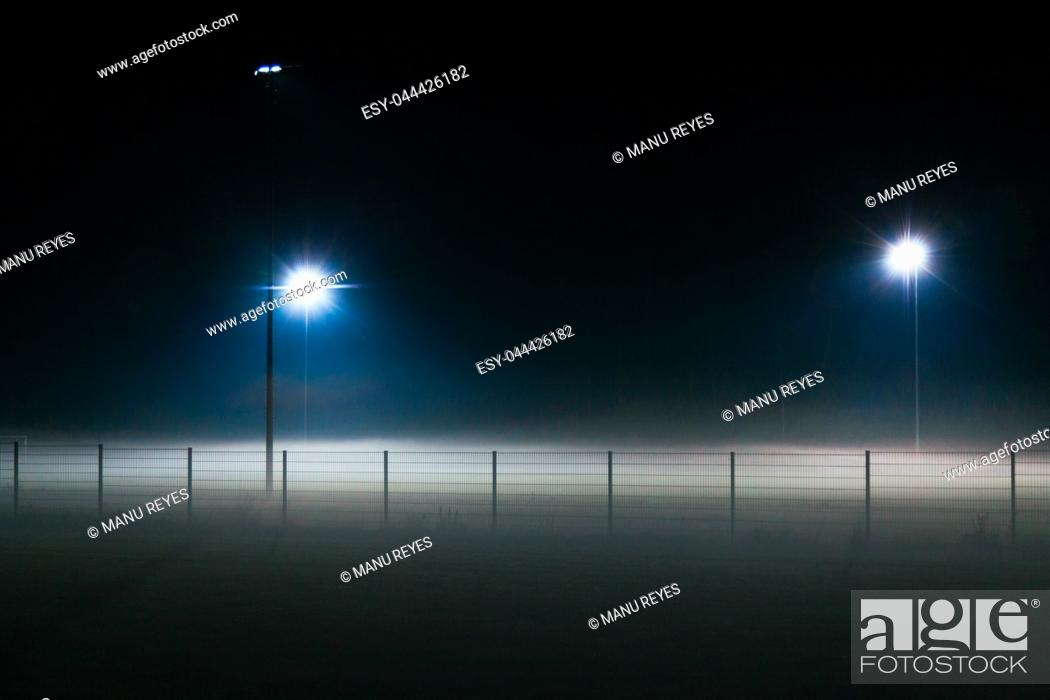 Stock Photo: Lonely football field covered by fog at night only illuminated by spotlights. Baviera, Germany.