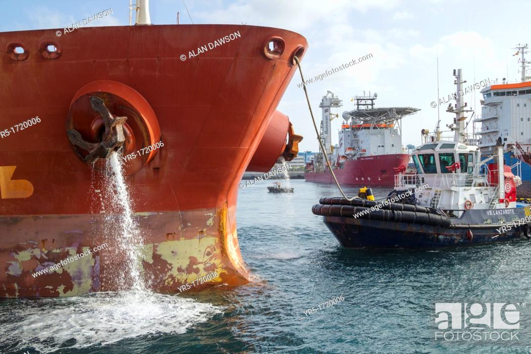 Oil tanker emptying ballast water as tug boat guides ship onto berth