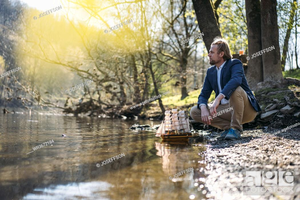 Imagen: Male entrepreneur looking away while crouching by model boat at riverbank in park.