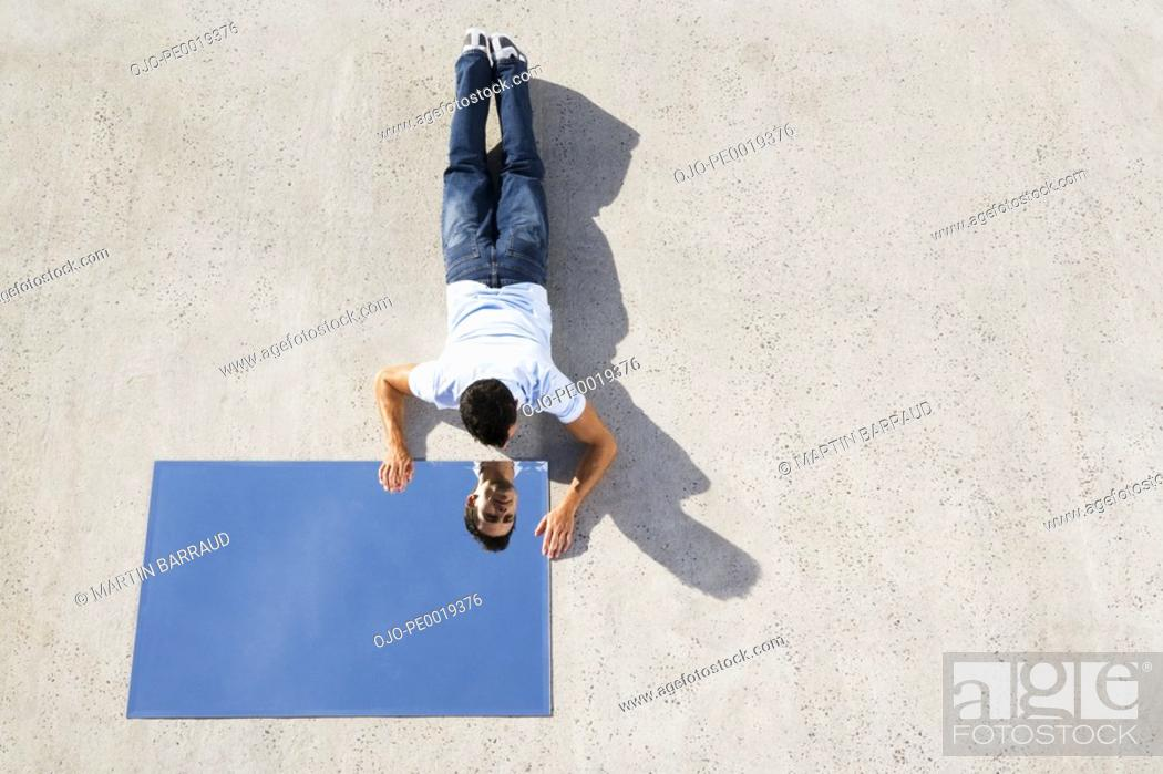 Stock Photo: Man lying down on ground with mirror and reflection.