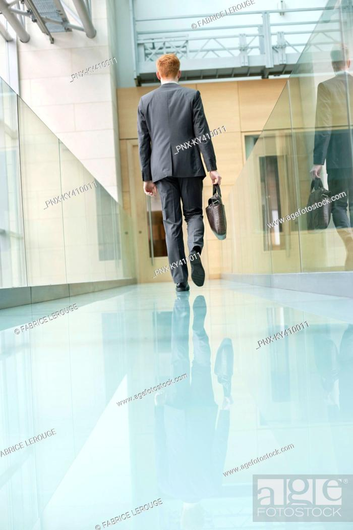 Stock Photo: Rear view of a businessman walking in an office corridor.
