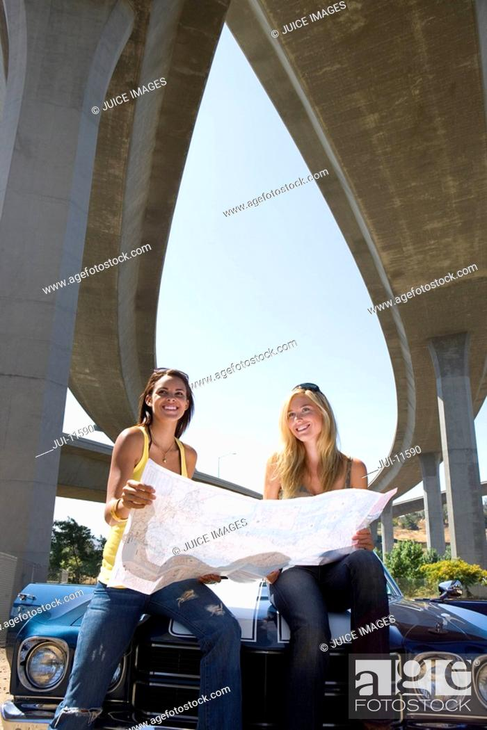 Stock Photo: Two young women on bonnet of car looking at road map beneath overpass, smiling, portrait, low angle view.