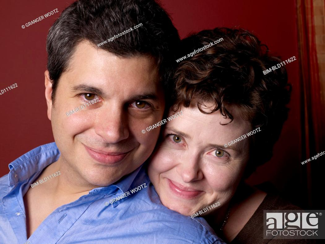 Stock Photo: Smiling couple hugging indoors.