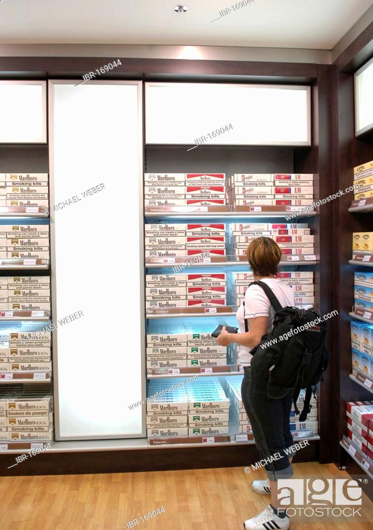 Customer in front of cartons of Cigarettes in Duty-Free Shop Airport
