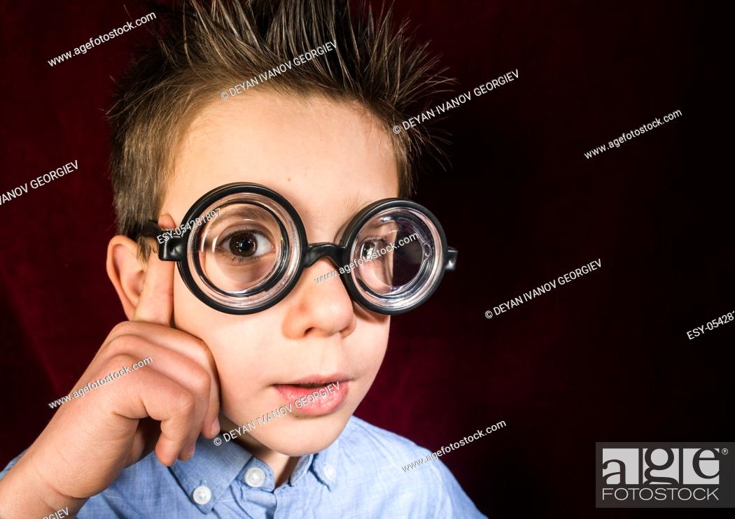 Stock Photo: Thinking child with big glasses. Red curtain background.