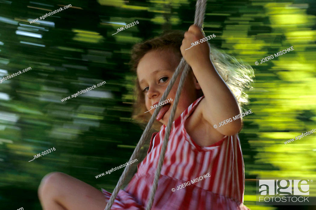 Stock Photo: A little girl, 1-5 years old, swinging in the garden in summer.