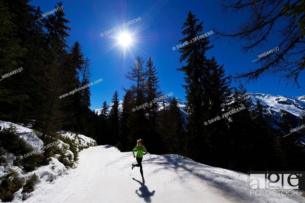 Stock Photo: A jogger running on snowy mountains.