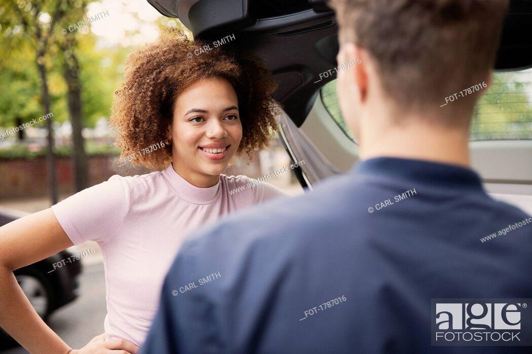 Stock Photo: Young couple talking at car.