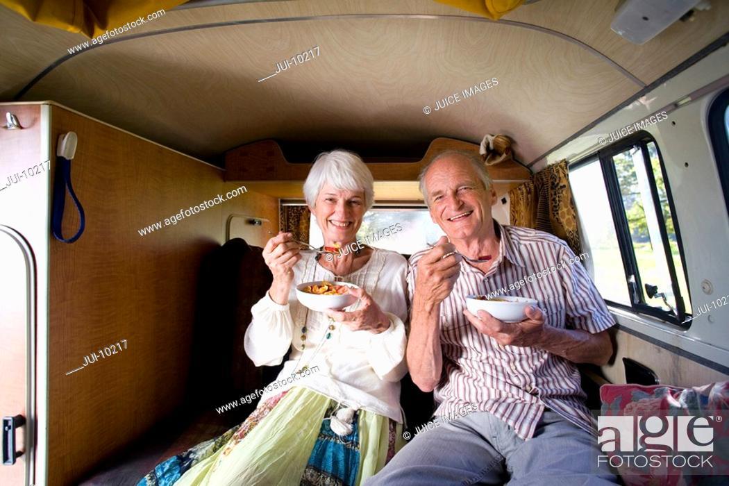 Stock Photo: Senior couple eating breakfast in back of camper van, smiling, portrait.