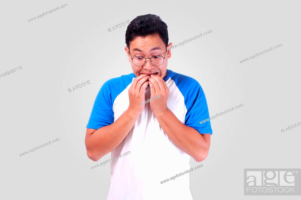 Stock Photo: Portrait of young funny Asian man biting his nails as if he is worried afraid of something bad.
