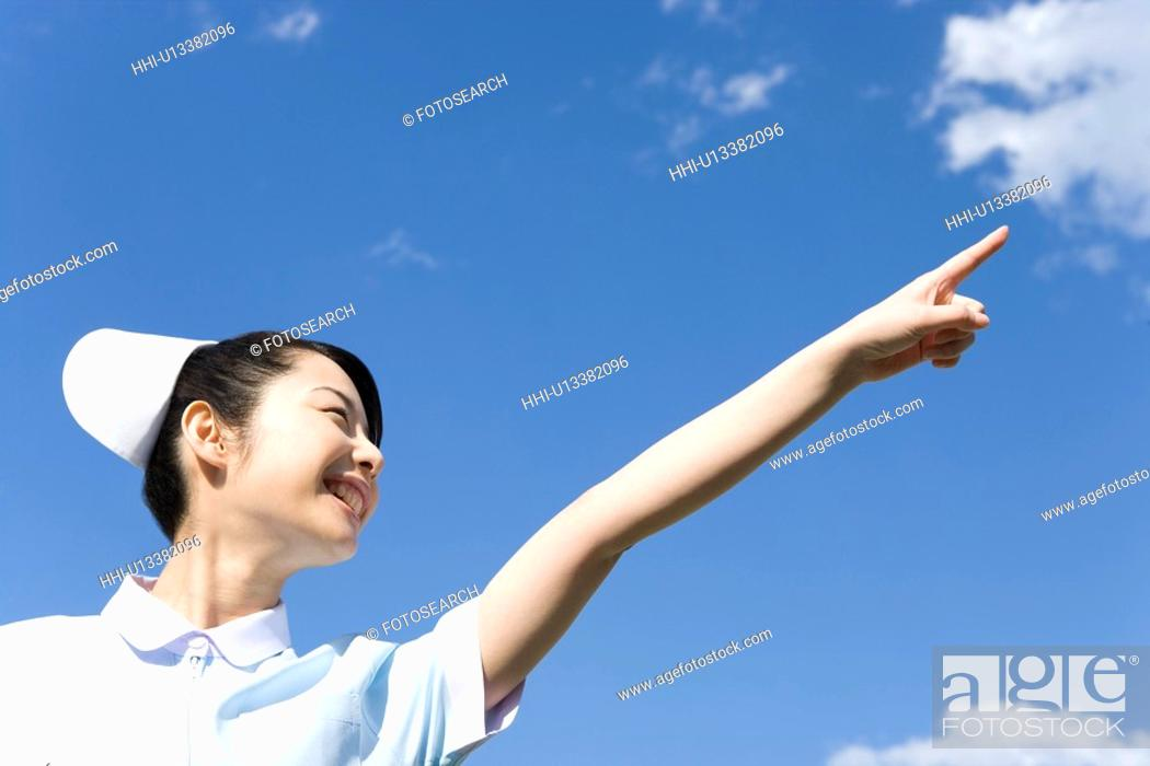 Stock Photo: Nurse smiling and pointing up under the blue sky, low angle view.