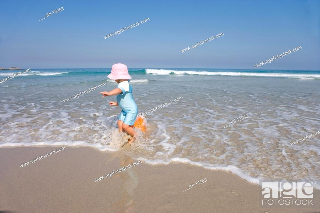 Stock Photo: Girl 1-3 playing in waves on beach.