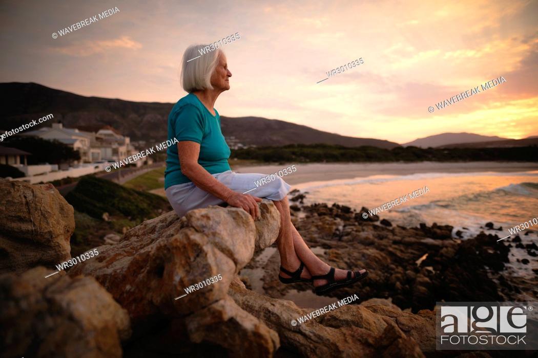 Stock Photo: Senior woman sitting on seaside rocks.