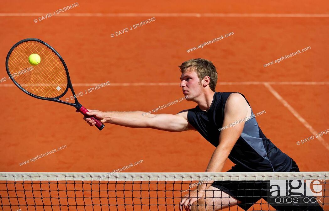 Stock Photo: A tennis player at the net stretches to play ball.