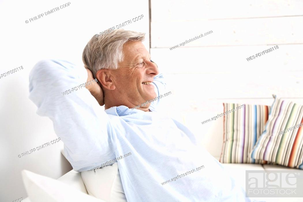 Stock Photo: Spain, Senior man relaxing on couch, smiling.