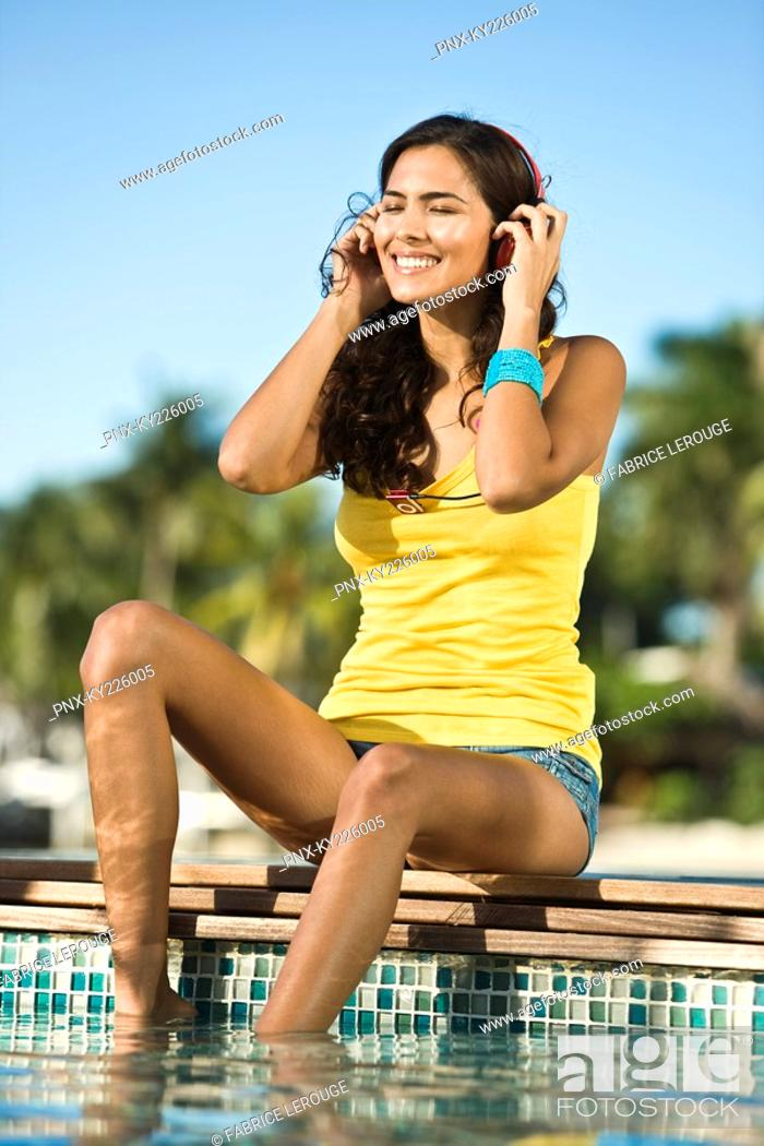 Stock Photo: Woman listening to headphones at the poolside.