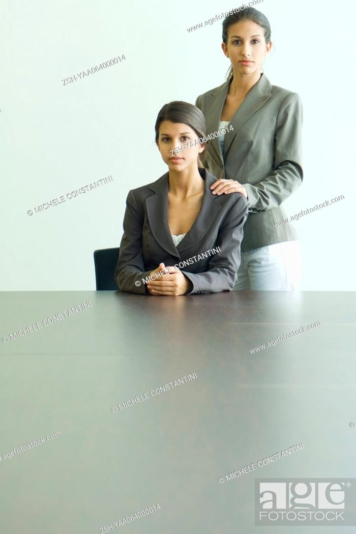 Stock Photo: Teenage girl standing behind twin sister, hands on shoulders, both dressed in suits and looking at camera.