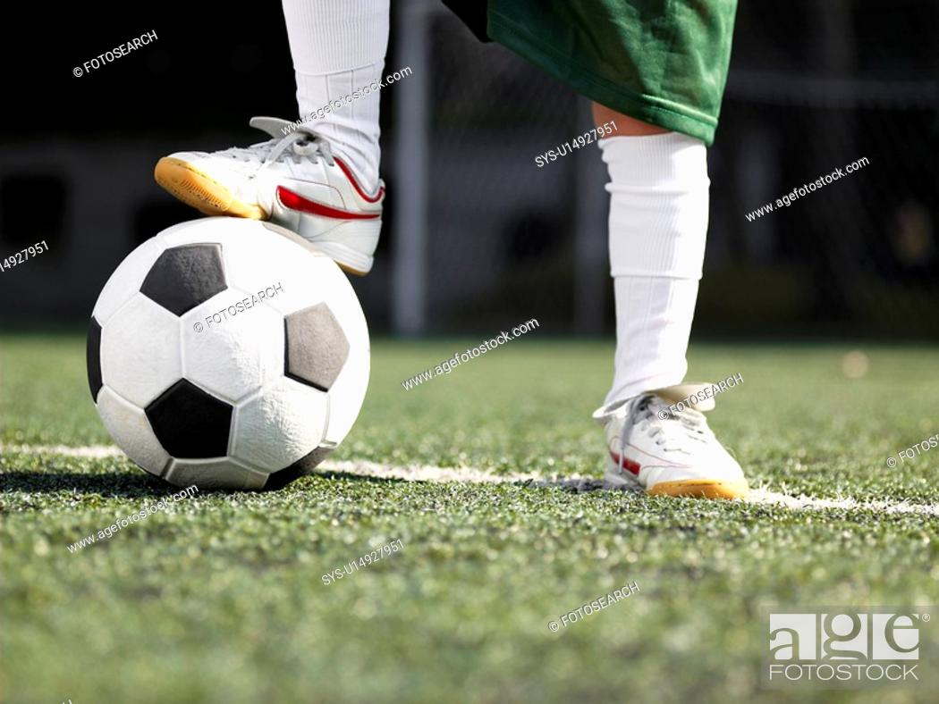 Stock Photo: Child's foot on soccer ball close-up.
