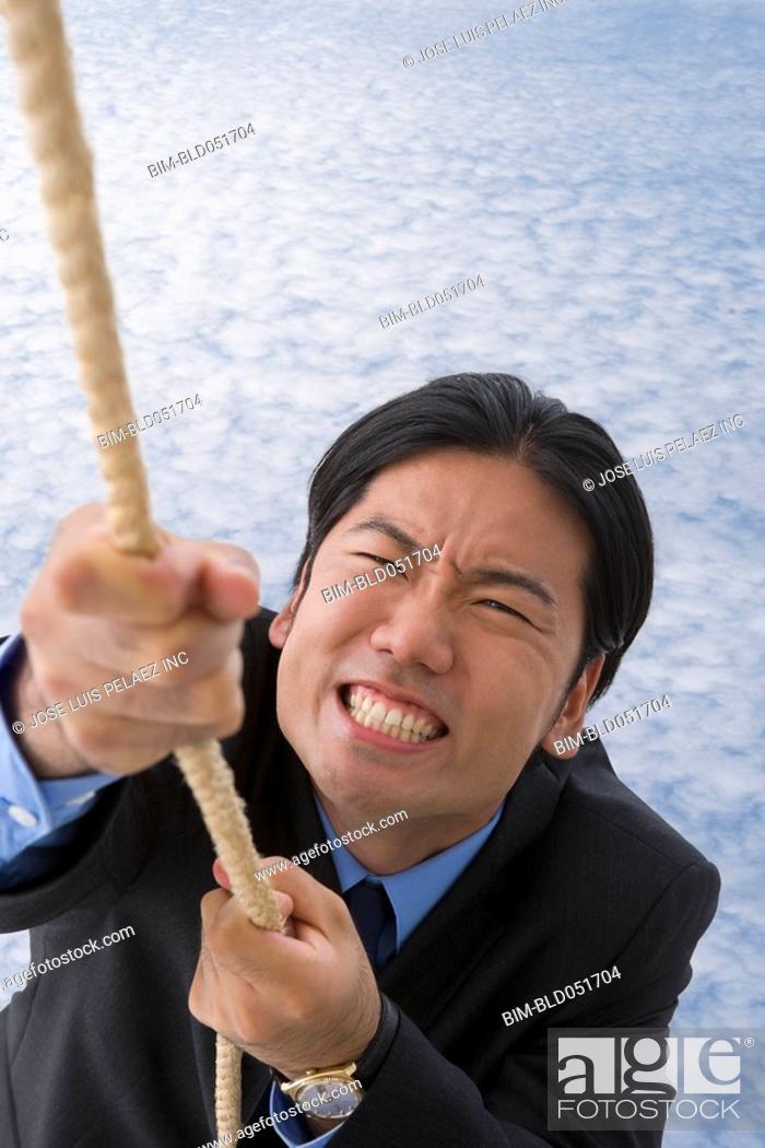 Stock Photo: Asian businessman climbing up rope.