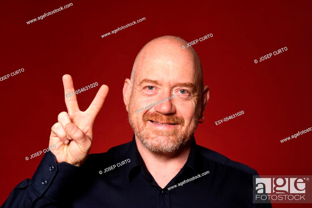 Stock Photo: man with sign victory on red background.