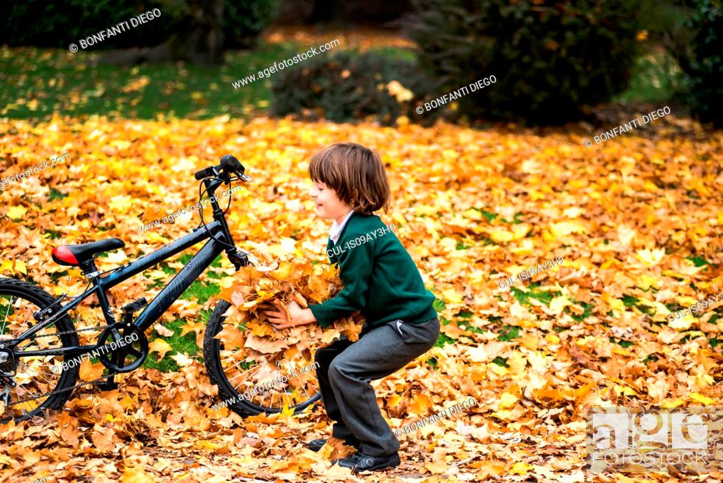 Stock Photo: Boy in park with bike playing in autumn leaves.
