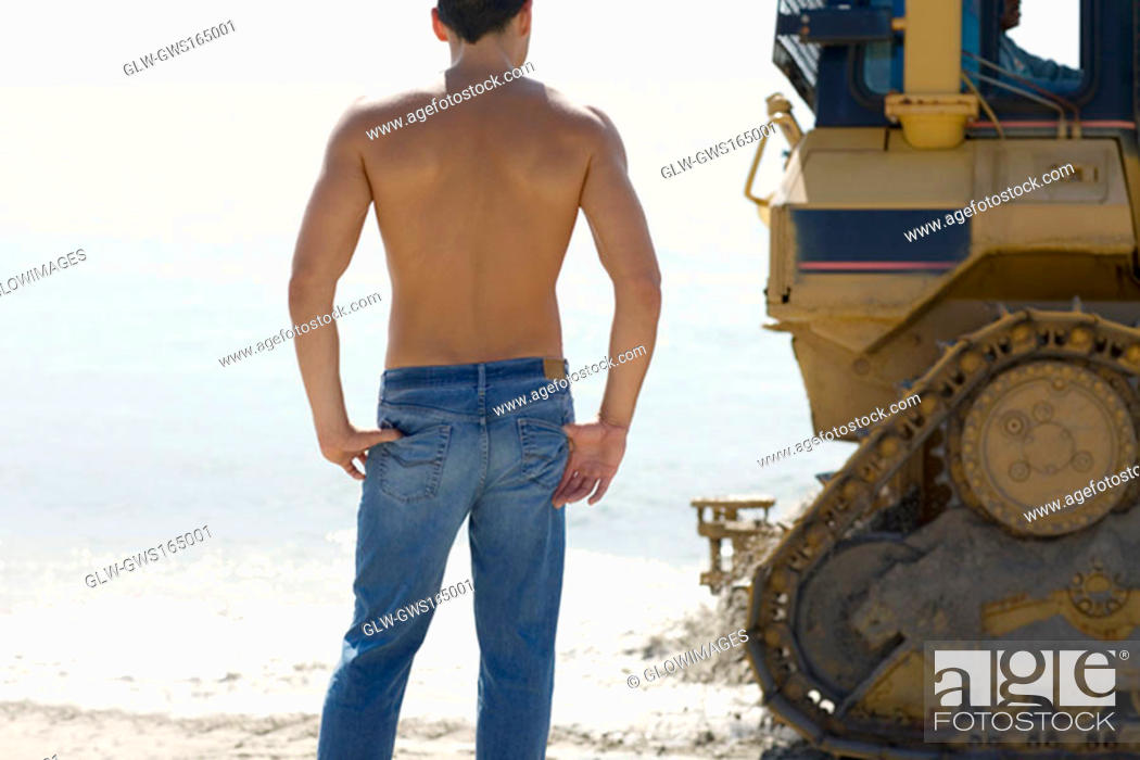 Stock Photo: Rear view of a mid adult man standing behind an earth mover on the beach.