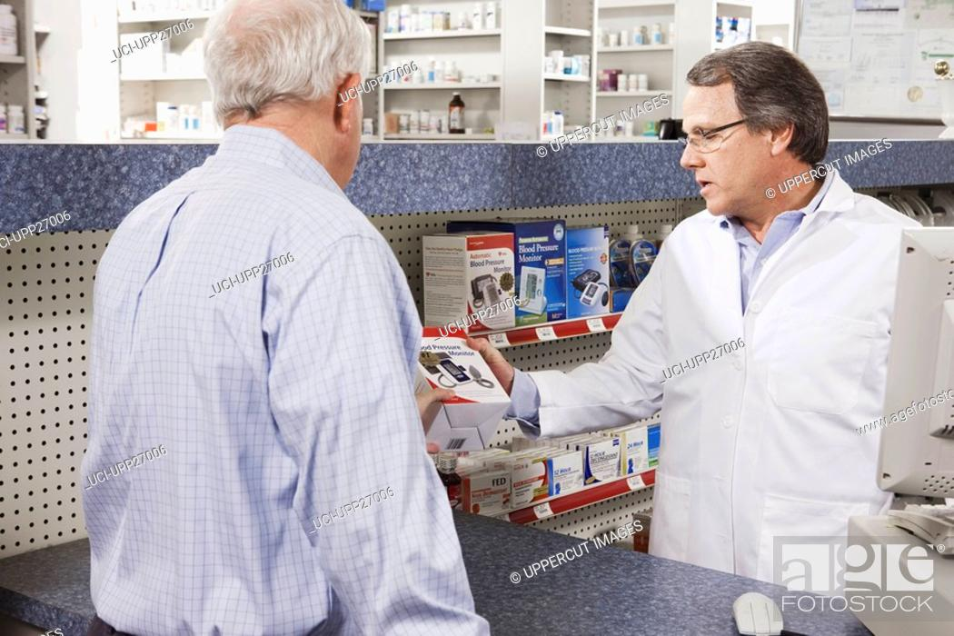 Stock Photo: Pharmacist showing blood pressure monitor to customer.