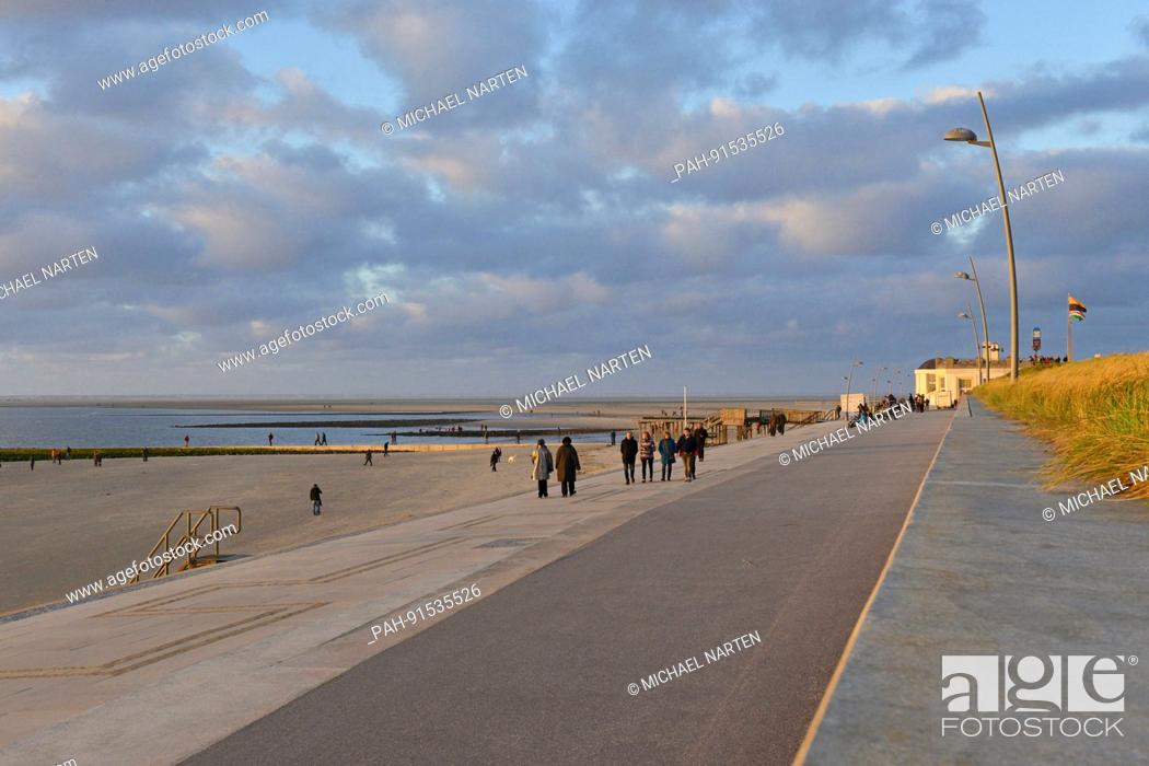 Stock Photo: Holidaymaker on Borkum's promenade in the evening light with view to the beach under a cloudy sky, 29 October 2016 | usage worldwide.