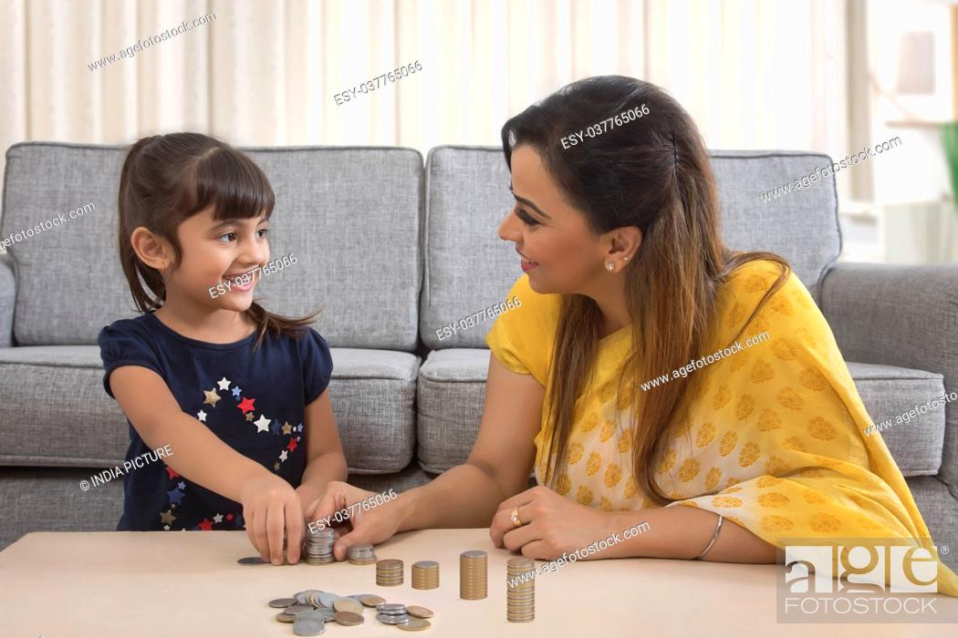 Stock Photo: Smiling mother and daughter stacking coins sitting together.