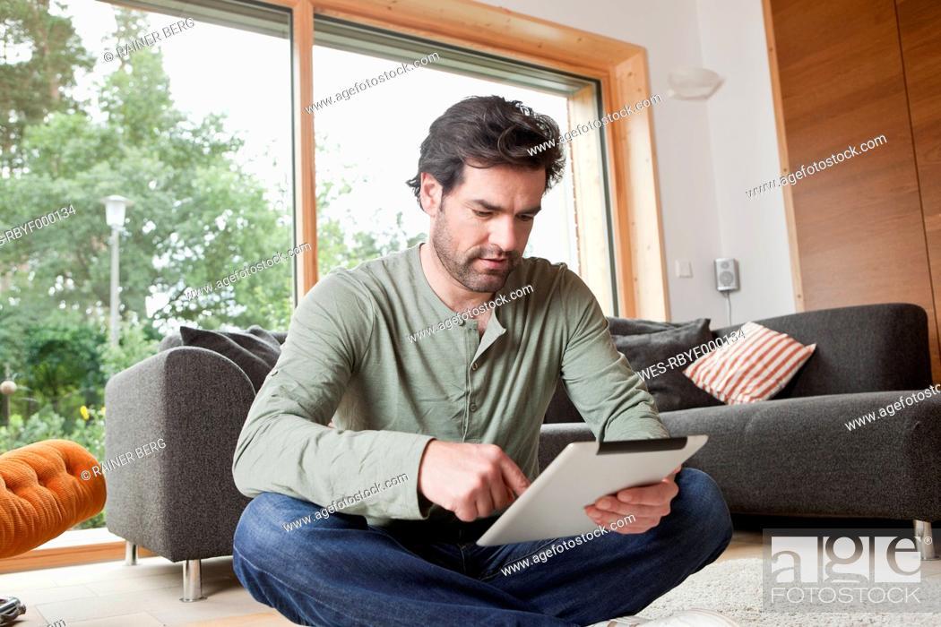Stock Photo: Germany, Bavaria, Nuremberg, Mature man using digital tablet in living room.
