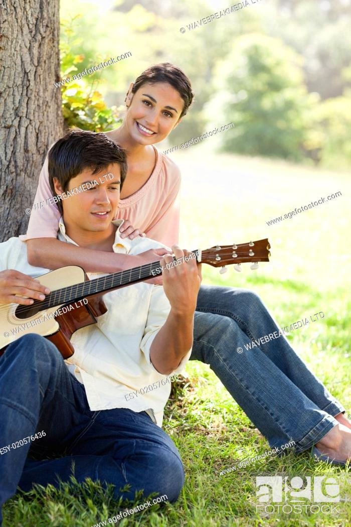 Imagen: Woman holding her friend as her plays the guitar.
