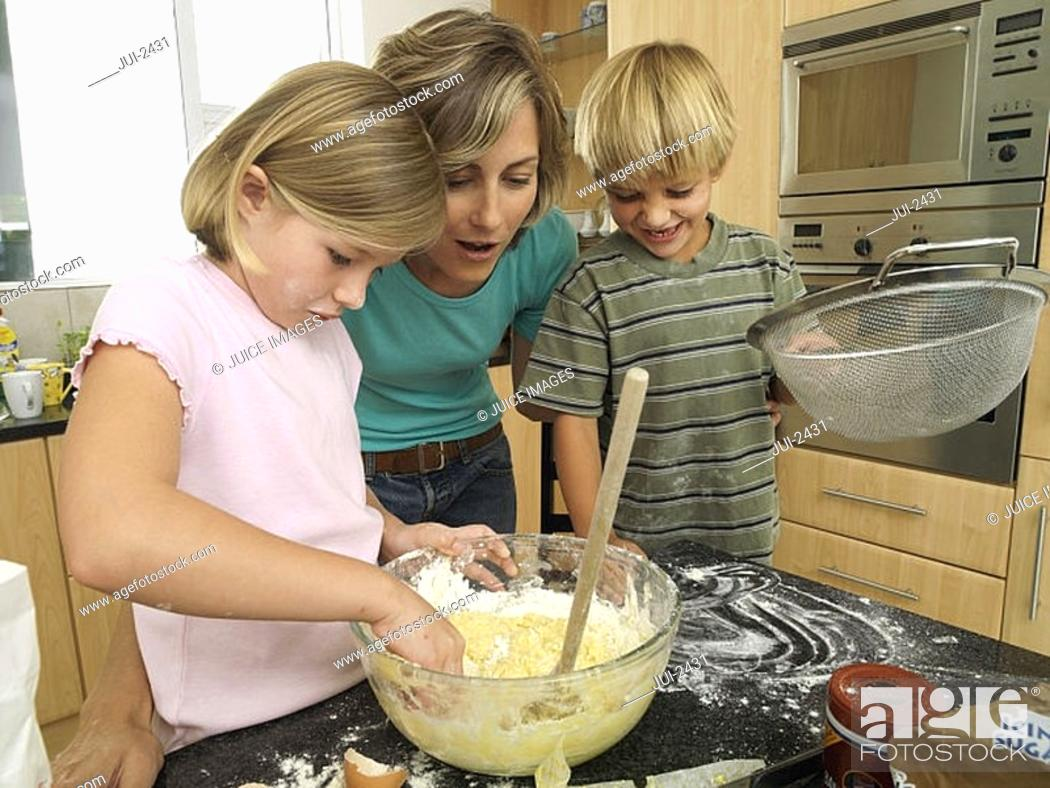 Stock Photo: Mother and children 5-8 making cake mix in kitchen, boy holding sieve, girl dipping hand in bowl.