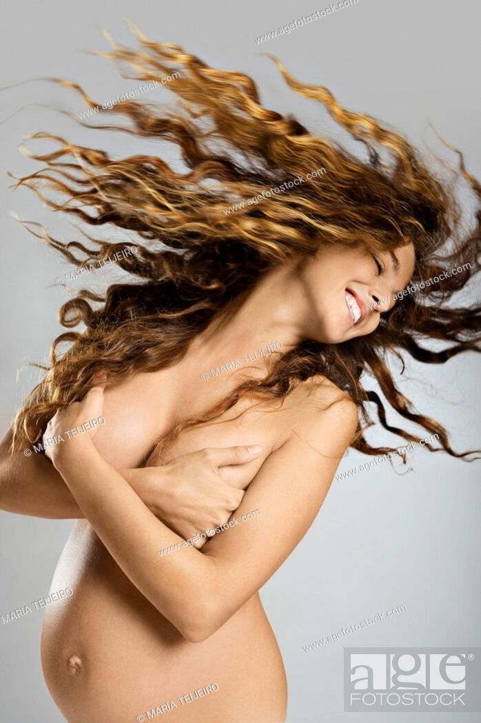 Stock Photo: Nude, pregnant woman swing her long hair.