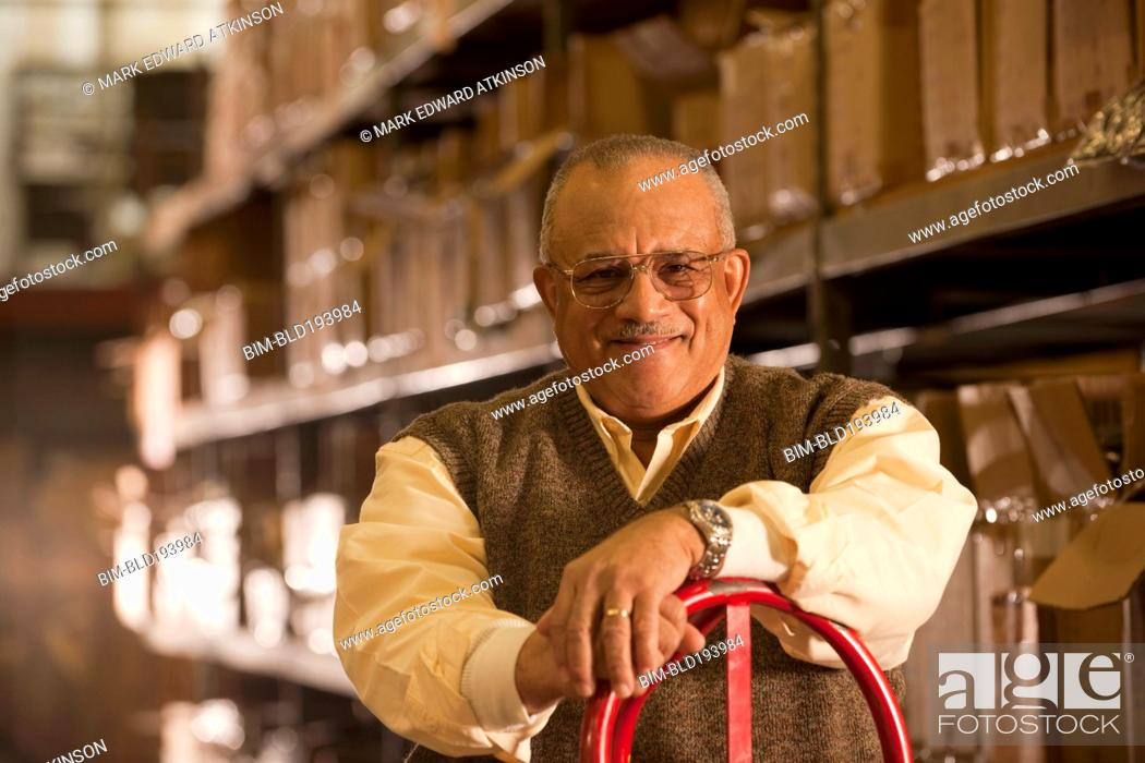 Stock Photo: Mixed race man with hand truck in warehouse.