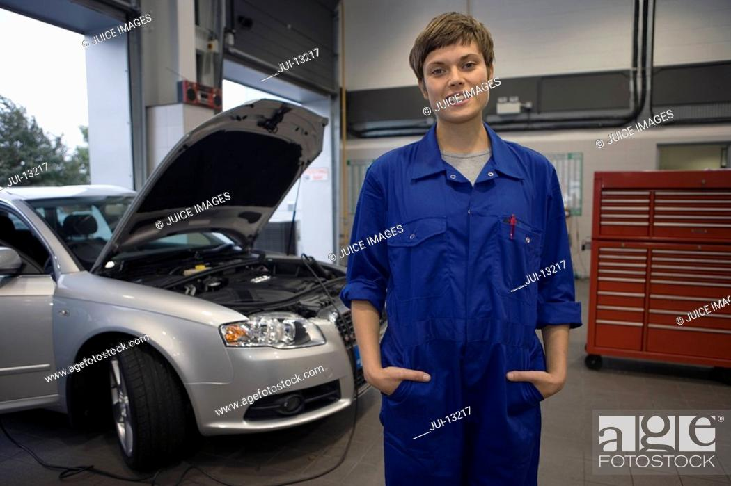 Stock Photo: Female mechanic with hands in pockets, car with open bonnet in background, smiling, portrait.
