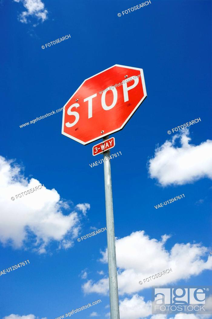 Stock Photo: Stop sign with blue cloudy sky.
