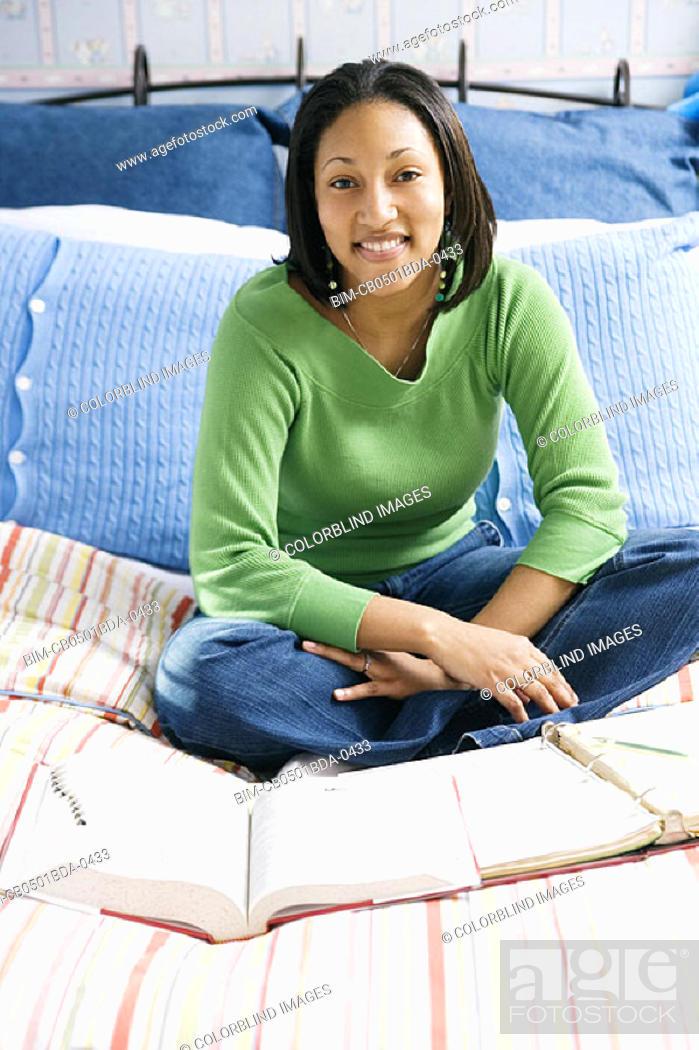 Stock Photo: Girl in bedroom doing homework.