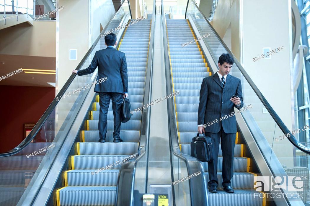 Stock Photo: Businessmen standing on escalators.