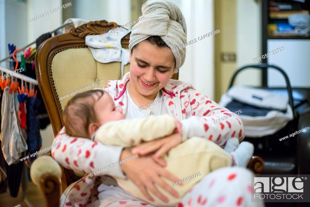 Imagen: little girl with baby in her arms sitting in an armchair at home towel in her hair clothes hanging on the background.