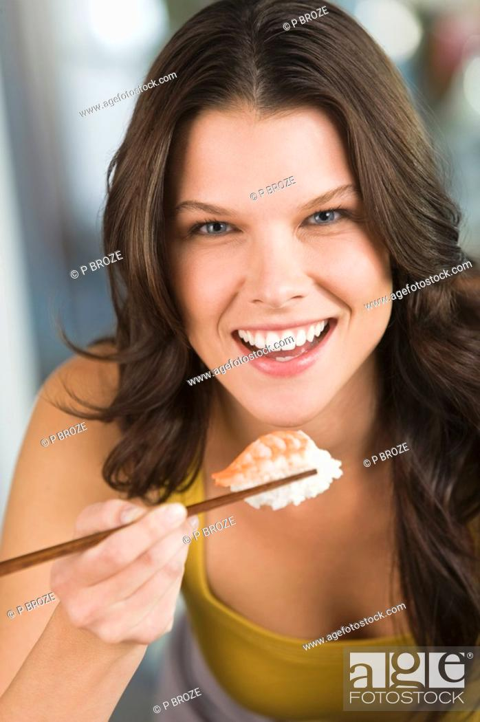 Stock Photo: Woman eating sushi.
