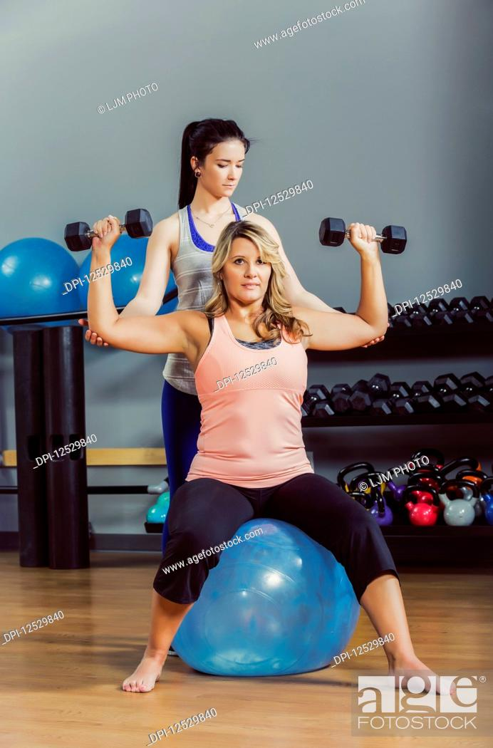 Stock Photo: An attractive middle-aged women working out using free weights on a balance ball at the gym with her personal trainer giving assistance; Spruce Grove, Alberta.