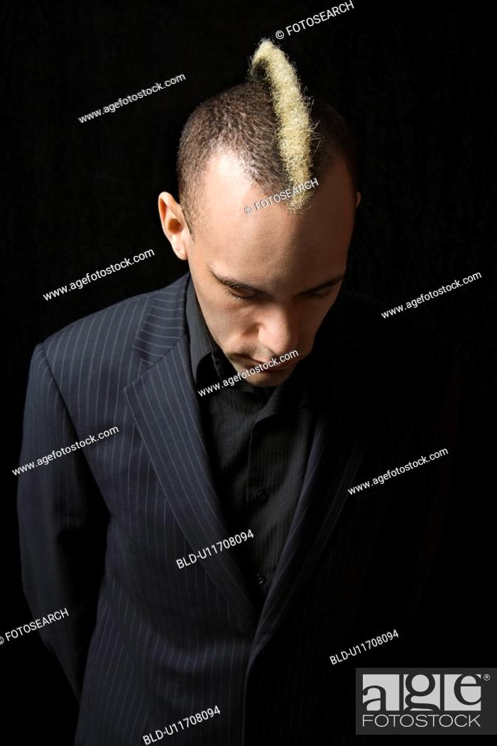 Stock Photo: Man in suit with mohawk looking down.