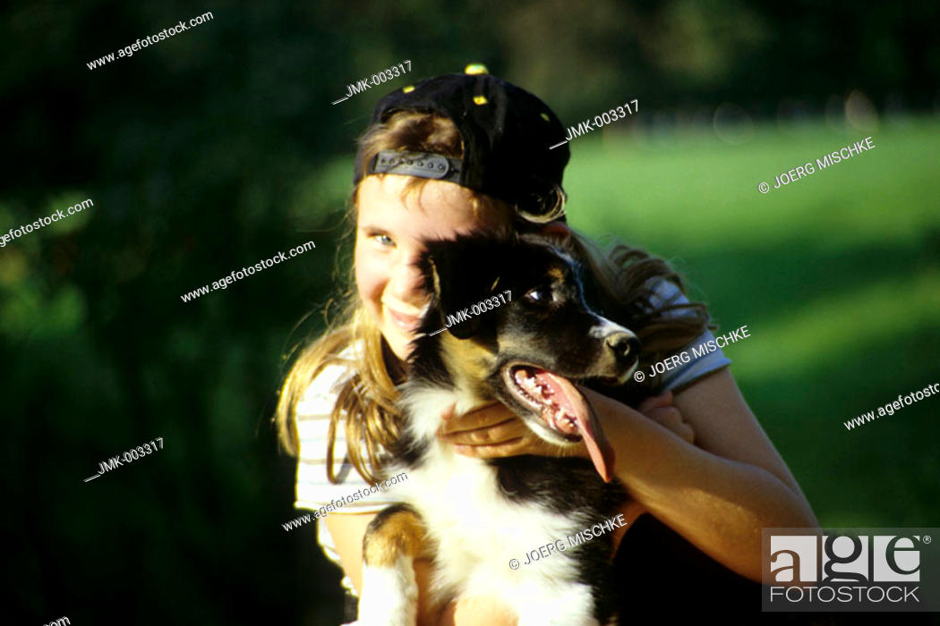 Stock Photo: A girl, 5-10 years old, with a dog outside in summer.