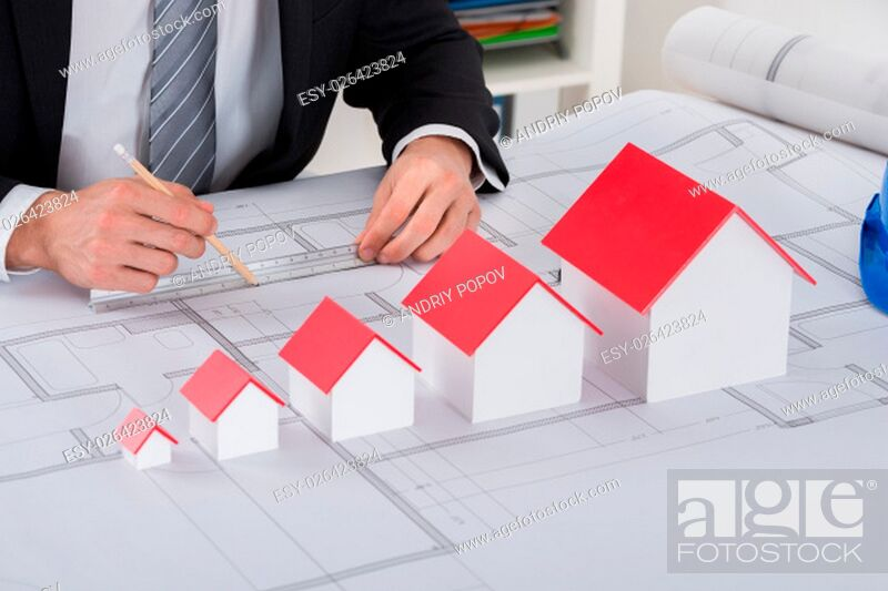 Stock Photo: Close-up Of Male Architect Hand With House Models Working On Blueprint In Office.