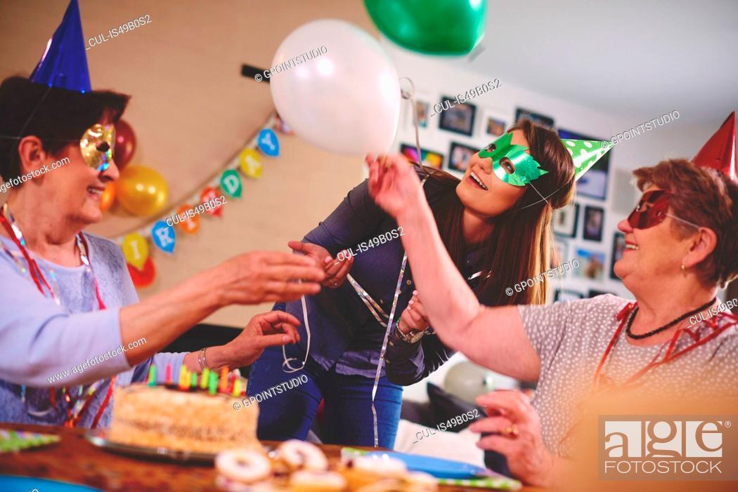 Stock Photo: Senior women waving balloons at birthday party.